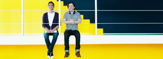 Deux hommes heureux devant un mur jaune dans un bureau