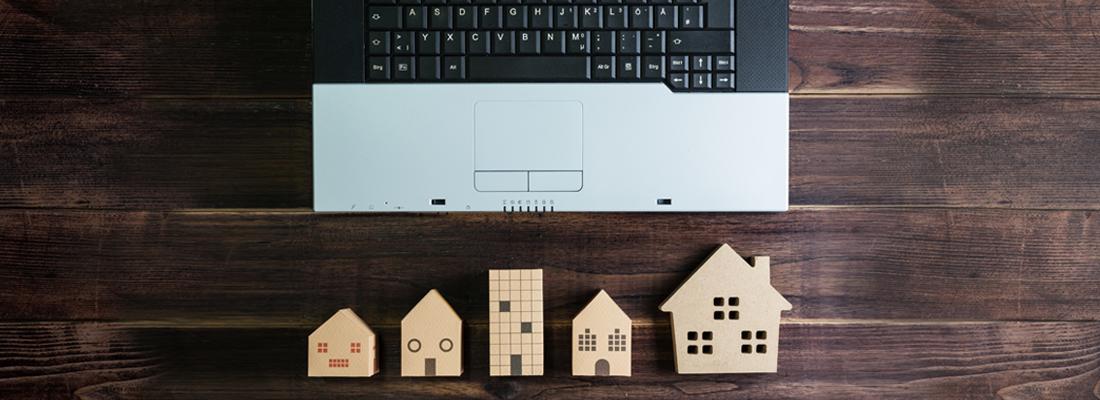 Træmodeller af huse ved siden af en laptop