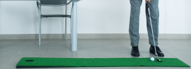 A man playing mini golf in his office