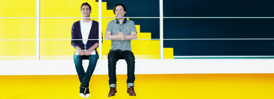 Двое радостных мужчин на желтом фоне в офисе