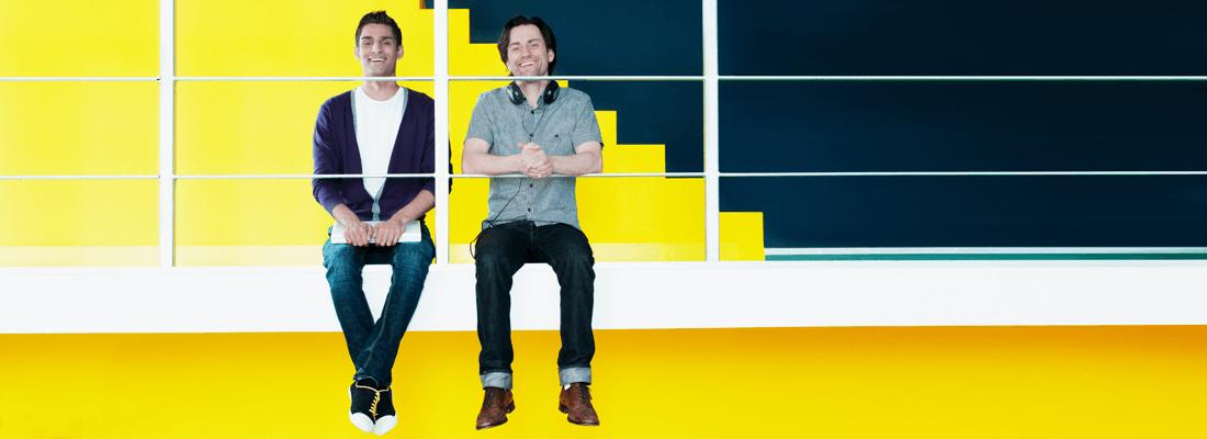 Zwei fröhliche Männer vor gelbem Hintergrund in einem Büro
