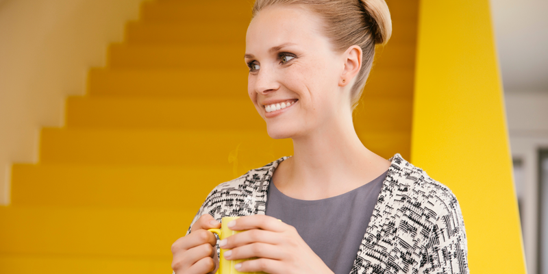 A happy woman against a yellow background