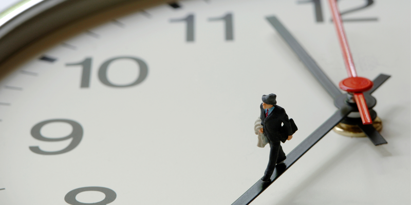 A model of a tiny man walking on the hands of a clock