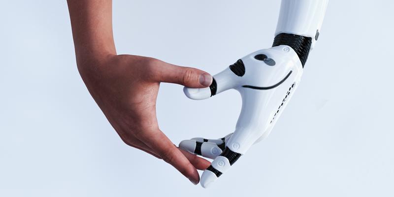 指でハートを作っているロボットの腕と人間の腕