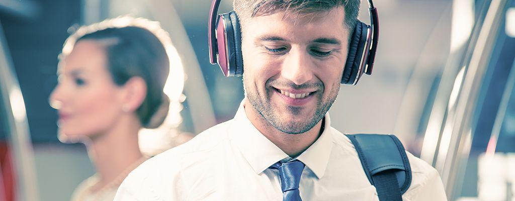 Elegant man wearing headphones during his journey by train