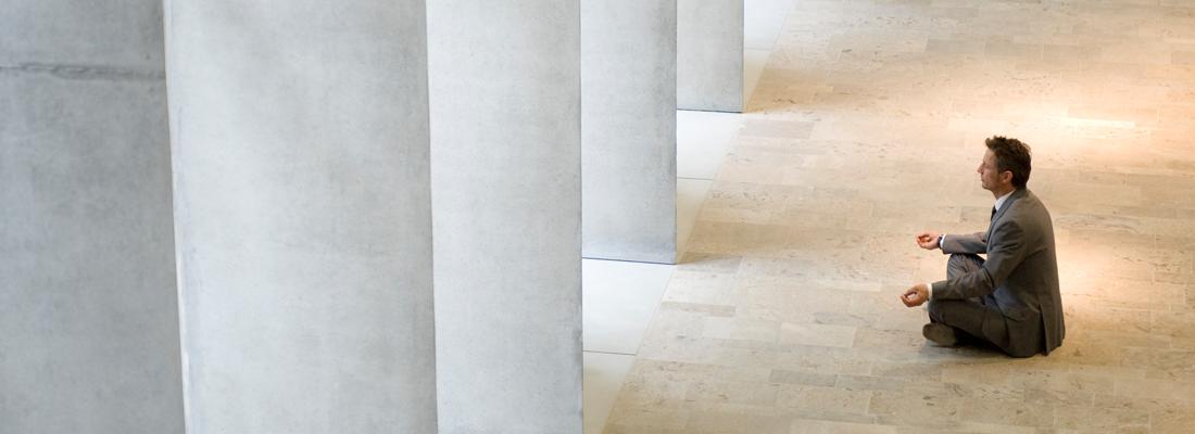 Man meditating in marble hallway