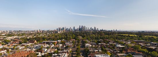 Aerial of Melbourne CBD skyline with suburban Melbourne residential area in the foreground.